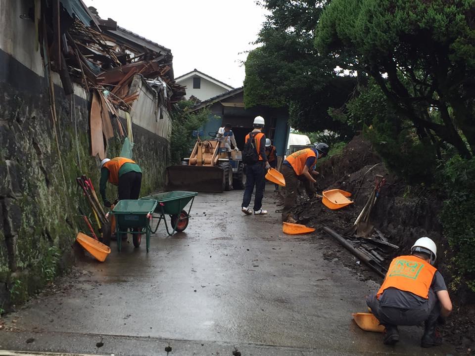 ブロック塀が崩れて土が落ちてしまった家の土や瓦の片付け。住民の方もローダー(奥)を使いつつ、一緒に作業しました。